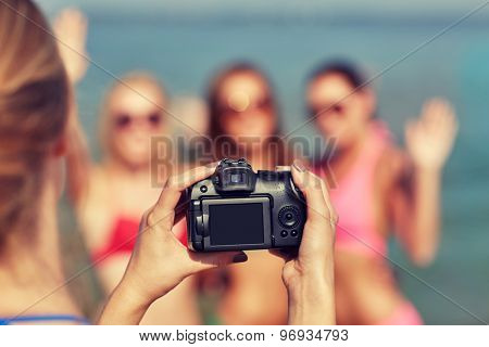summer vacation, gesture, technology, travel and people concept - close up of smiling young women photographing by camera and waving hands on beach