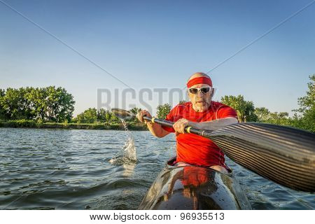 senior male paddler training in a racing sea kayak with a wing paddle on a lake, motion blur of paddle