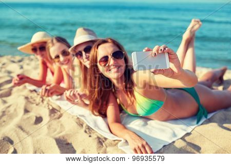 summer vacation, travel, technology and people concept - close up of smiling women in sunglasses and hats making selfie with smartphone on beach