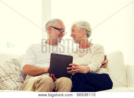 family, technology, age and people concept - happy senior couple with tablet pc computer at home