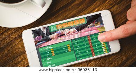 Gambling app screen against smartphone on desk