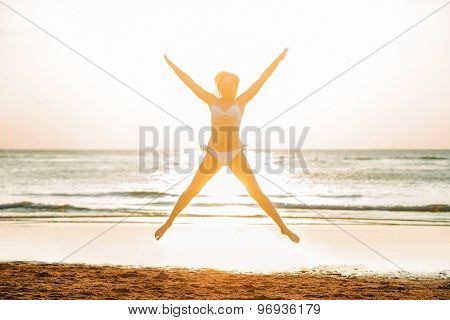 Beautiful woman standing in front of the sunset on the beach.
