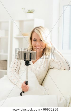 Attractive grimacing girl taking selfie holding a selfie stick.