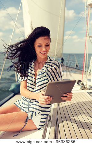 vacation, holidays travel, sea and technology concept - smiling woman sitting on yacht with tablet pc