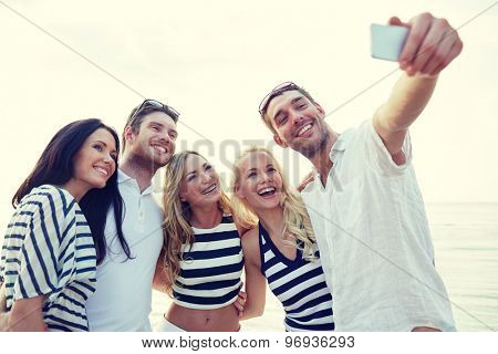 summer, sea, tourism, technology and people concept - group of smiling friends with smartphone on beach photographing and taking selfie