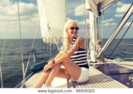 vacation, holidays, travel, sea and people concept - smiling young woman sitting on yacht deck