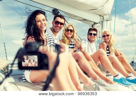 vacation, travel, sea, friendship and people concept - smiling friends sitting on yacht deck and photographing
