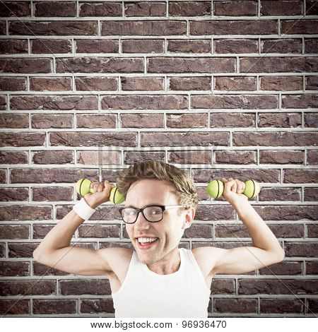 Nerd lifting weights against red brick wall