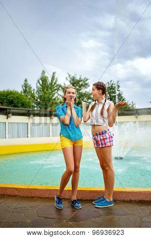 Best Girlfriends Talking In Park Near The Fountain.