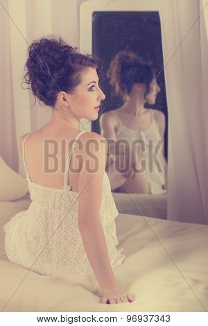 Girl Sits In Front Of A Mirror In Bedroom.