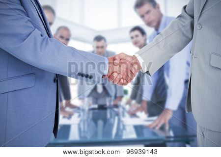 Side view of shaking hands against business colleagues discussing about work