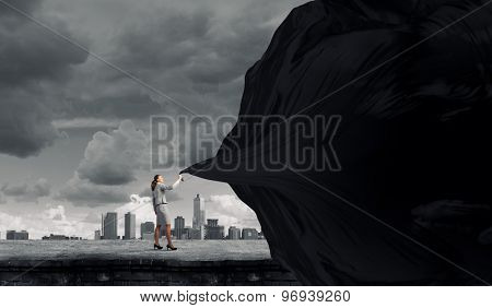 Young pretty businesswoman pulling clothing blank banner