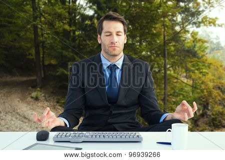 Calm businessman sitting in lotus pose against tarmac curved country road in forest