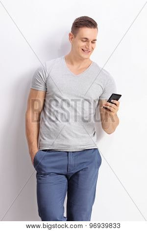 Vertical shot of a young man typing an SMS on his cell phone and leaning against a gray wall