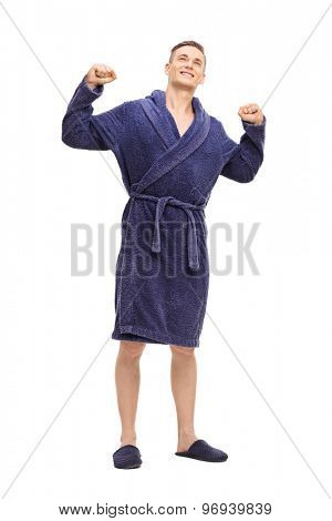 Full length portrait of a young man in a blue bathrobe stretching himself isolated on white background