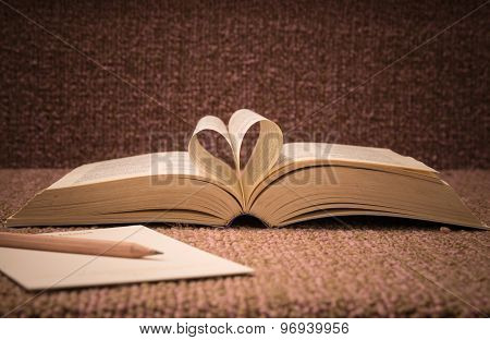 Pages Of Open Book Rolled In Heart Shape On Table