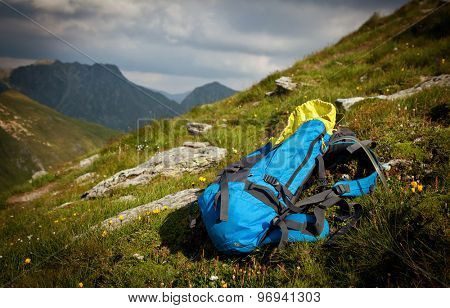 Backpack or rucksack balanced against a rock on top of a mountain summit