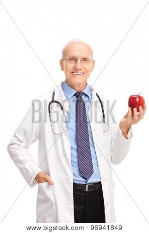 Vertical shot of a mature doctor holding a shiny red apple and looking at the camera isolated on white background
