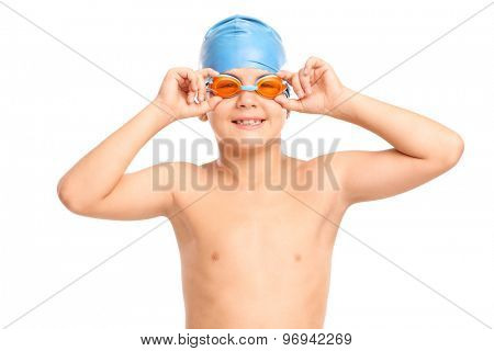 Little boy with orange swimming goggles and blue swim cap looking at the camera isolated on white background