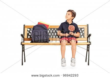Joyful little schoolboy sitting on a wooden bench and holding huge lollipop isolated on white background