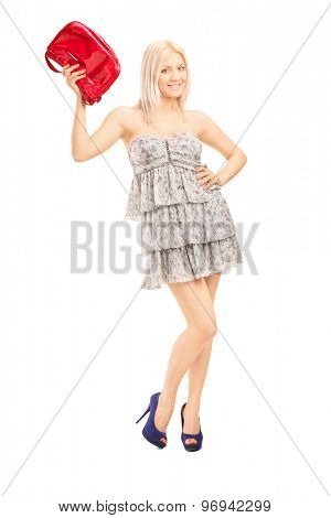 Full length portrait of a fashionable blond girl holding a red purse and looking at the camera isolated on white background
