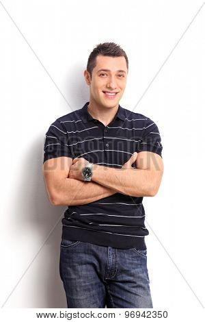 Vertical shot of a casual young guy in a striped black and white shirt leaning against a wall and looking at the camera isolated on white background