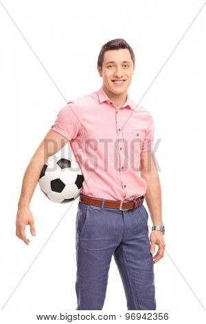 Vertical shot of a young casual guy holding a football and looking at the camera isolated on white background