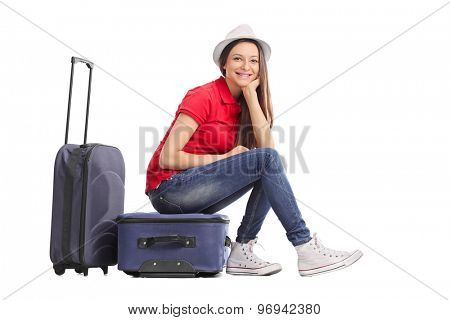 Beautiful girl with a stylish hat sitting on her luggage and looking at the camera isolated on white background