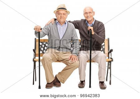 Studio shot of a two mature friends posing together seated on a wooden bench isolated on white background