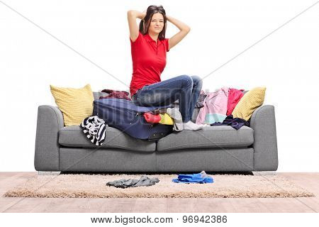 Frustrated young girl trying to pack a lot of clothes into one bag seated on a gray sofa isolated on white background