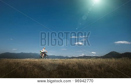 Father and son on bicycle under sunlight.