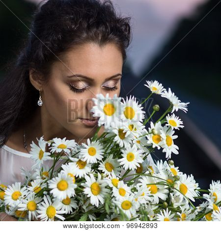 Young Beautiful Woman With Bouquet Of Camomile
