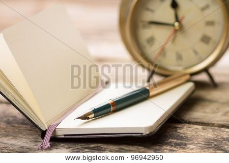 Open Notebook With Fountain Pen And Alarm Clock