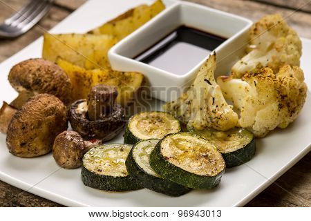 Roasted Vegetables With Sauce Served On Wooden Table