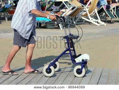 Senior Man Walking With Walker On The Beach In Summer