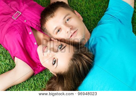 Young Beautiful Couple Laying Down Together On Grass In Park