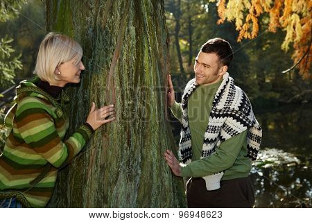 Happy casual caucasian couple playing catch me around tree outdoor at autumn forest. Having fun, hiking, smiling.