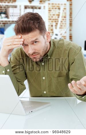 Young man sitting at desk, using laptop, looking desperate.