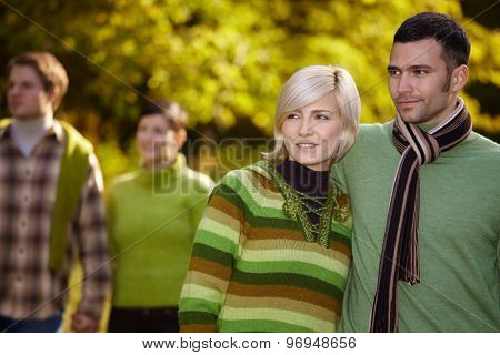 Happy casual caucasian couple with friends walking outdoor. Smiling, wearing warm clothes at autumn.