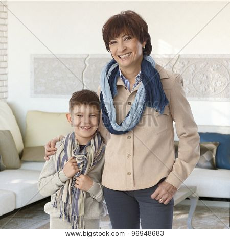 Grandmother and grandson embracing at home, smiling happy, looking at camera.
