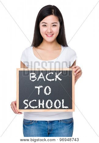 Student with chalkboard showing phrase of back to school