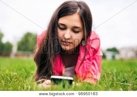 Beautiful girl writing sms on your smartphone