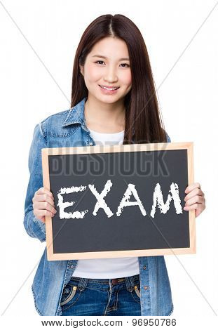 Young woman hold with chalkboard showing a word exam