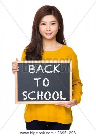 Woman with chalkboard showing phrase of back to school