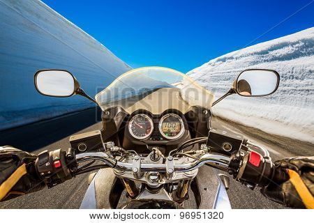 Biker rides a mountain road with high snow wall in Norway. First-person view.
