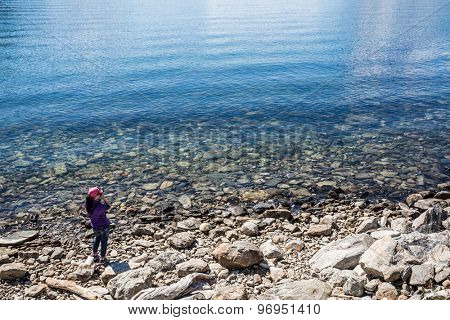 Nature photographer tourist with camera shoots lake. Beautiful Nature Norway.