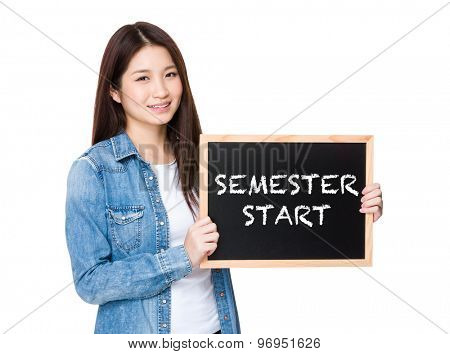 Woman with chalkboard showing phrase of semester start