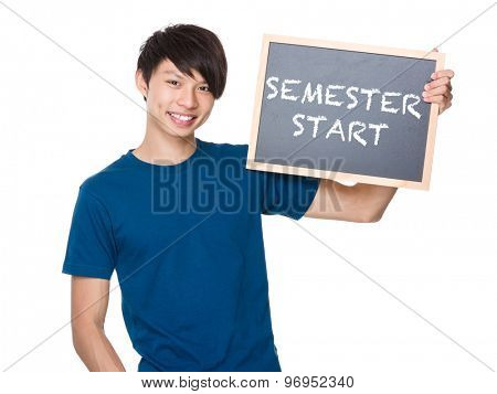 Asian man hold with blackboard and showing phrase of semester start