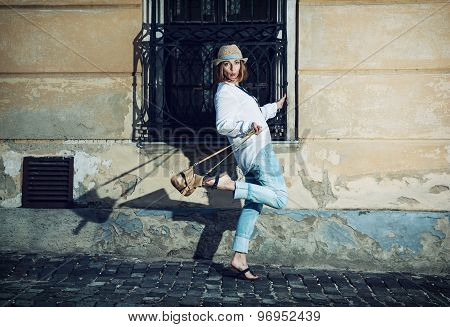 Pretty Woman In A Hat Poses With A Handbag And Whistles In The Courtyard