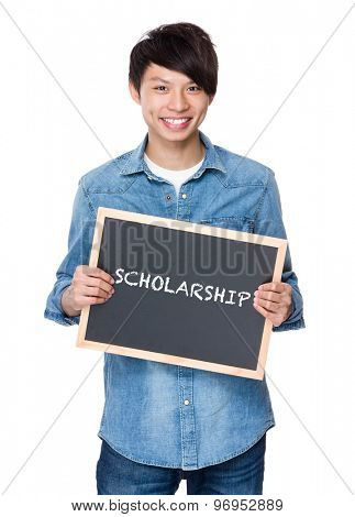 Asian young man with chalkboard showing a word scholarship